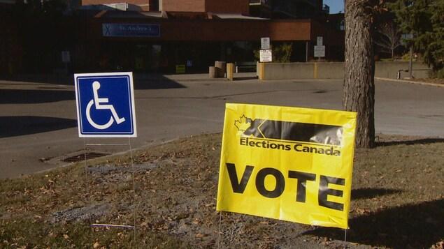 Une pancarte jaune sur laquelle il est inscrit : Élections Canada et Vote. À gauche, une pancarte bleue avec le symbole du handicap.