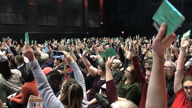 Une foule lève des cartons verts pour exprimer leur vote.