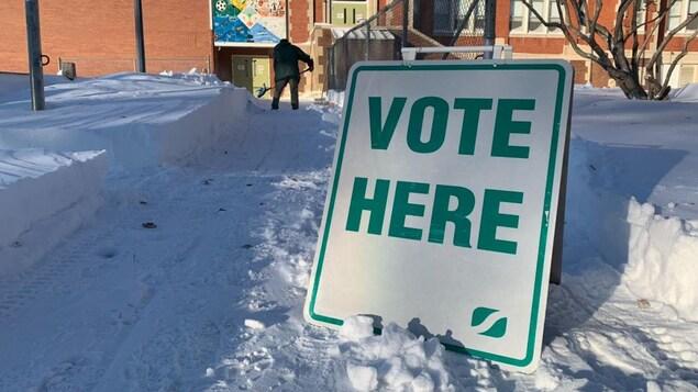 Une pancarte de bureau de vote avec beaucoup de neige.