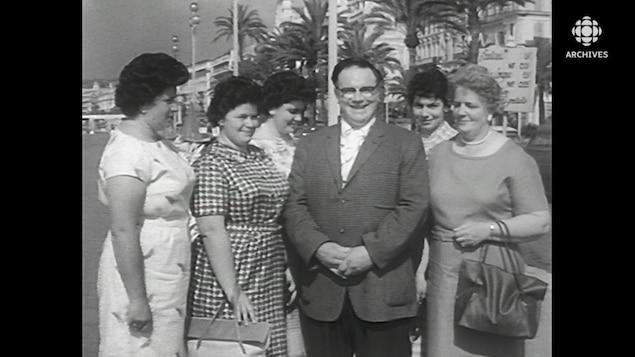 Un père de famille posant fièrement avec son épouse et ses quatre filles dans la vingtaine devant les palmiers de la Côte d'Azur.