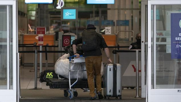 Un voyageur entre dans l'aéroport, chargé de bagages, en poussant un chariot.