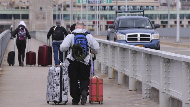 Des voyageurs traversent le pont Rainbow à Niagara Falls pour rentrer au Canada.