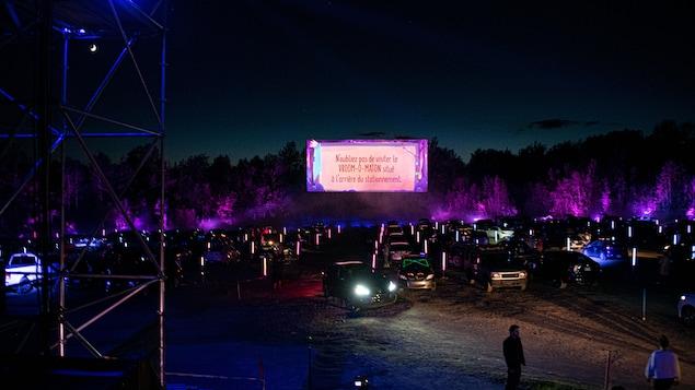 Des voitures stationnées devant l'écran.