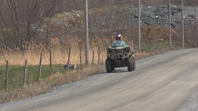 Un véhicule tout terrain circule sur un chemin public en longeant un champ.