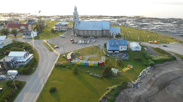 Vue aérienne des cabanes colorées des producteurs, sur un terrain vague à côté de l'église et d'un restaurant de Sainte-Luce.