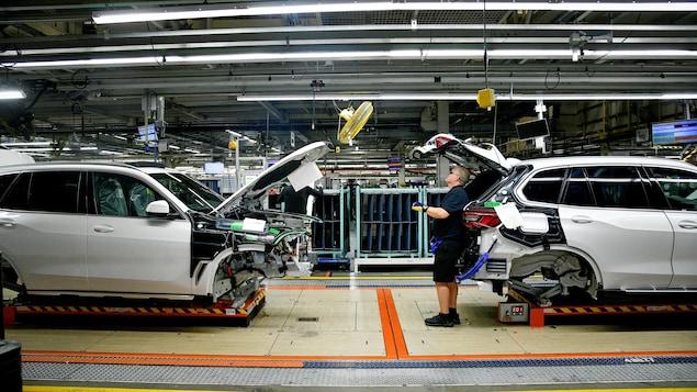 Un homme inspecte un VUS dans une usine.