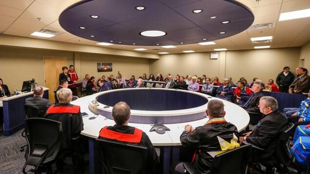 Deux magistrats assis d'un côté d'une grande table circulaire. En face d'eux se trouvent quelques dizaines de personnes assises dans des fauteuils.