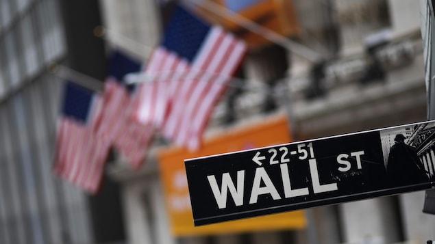 Le panneau de Wall Street photographié en gros plan avec, à l'arrière, une série de drapeaux américains suspendus à la façade de l'immeuble de la bourse, à New York.
