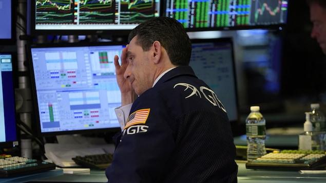 Un homme ayant l'air découragé se tient la tête en fixant l'écran d'un ordinateur.