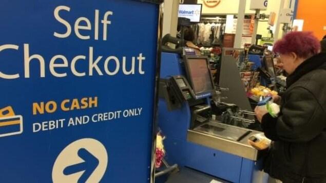 Une cliente passe à la caisse à Walmart.