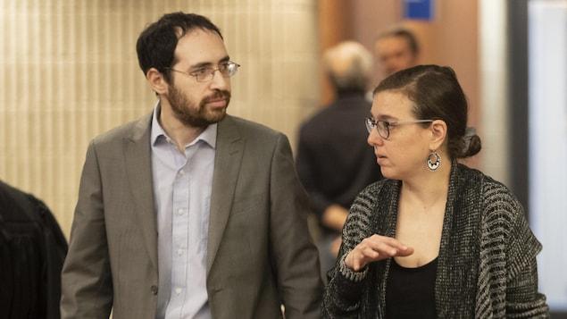 Deux personnes marchent dans un corridor du palais de justice de Montréal.