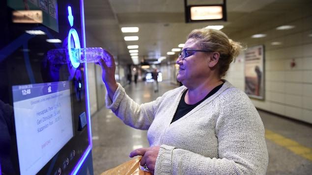 À Istanbul, une femme dépose des bouteilles de plastique dans une machine en échange de crédit sur sa carte de métro.