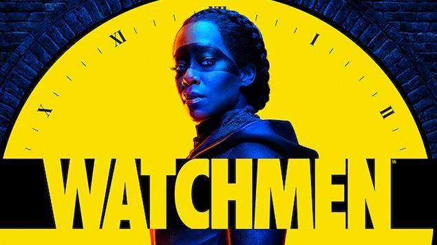 Une femme maquillée devant le cadran d'une horloge, avec le logo de l'émission Watchmen dans le bas de l'écran.
