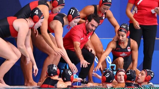 Les joueuses de l'équipe féminine canadienne de water-polo sont rassemblées sur le bord de la piscine avec leur entraîneur.
