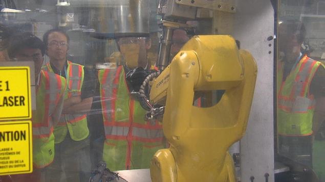 Un robot de production observé par différentes personnes vêtues de dossards de sécurité.