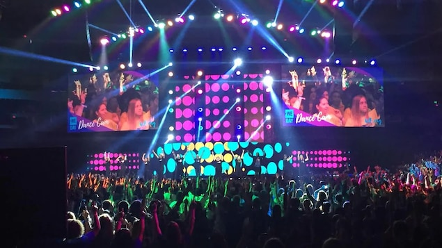 Une foule dans une salle de concert avec des lumières et des écrans.
