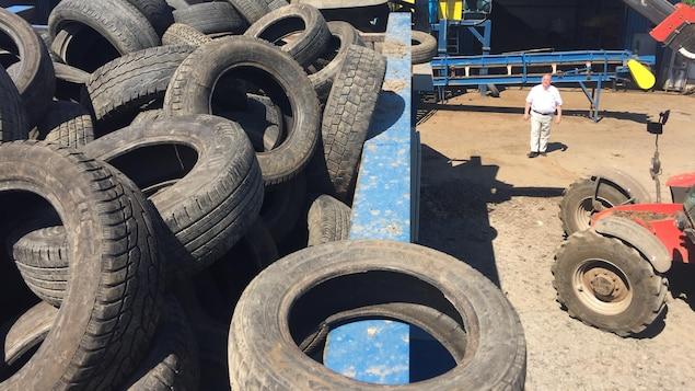 Un homme marche à côté d'un conteneur contenant des pneus