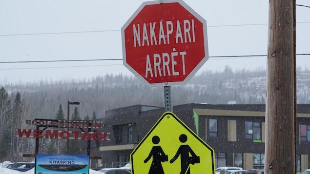 Un panneau d'arrêt en français et en atikamek devant l'école.