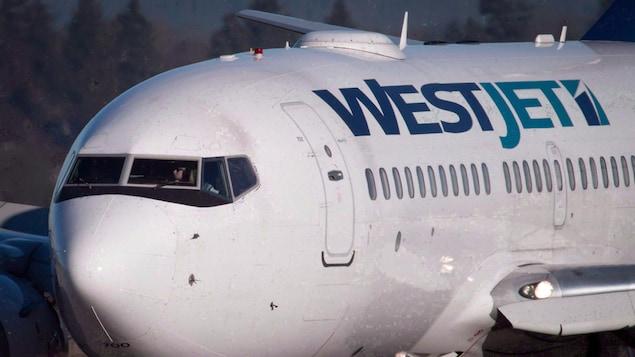 Un gros plan d'un avion du transporteur WestJet, vu de l'extérieur. On voit un pilote assis dans la cabine.