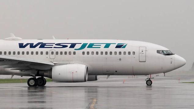 Un avion WestJet sur une piste d'atterrissage.