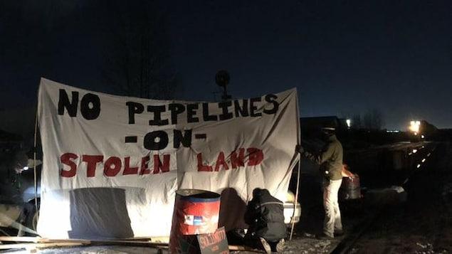 Une voie ferrée bloquée par des voitures. Des personnes installent une banderole où il est écrit: pas de pipeline sur une terre volée.