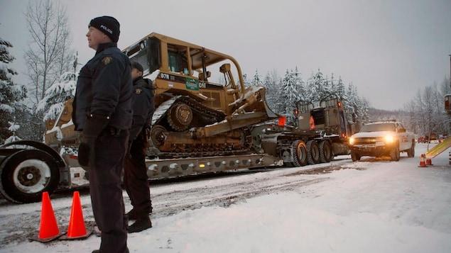 Des policiers, en hiver, se trouvent au bord d'une route dans la forêt. Des machines lourdes sont vues près d'eux.