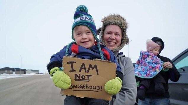 Un petit garçon, porté par sa mère, a dans la main une pancarte avec le message suivant : « Je ne suis pas dangereux ».