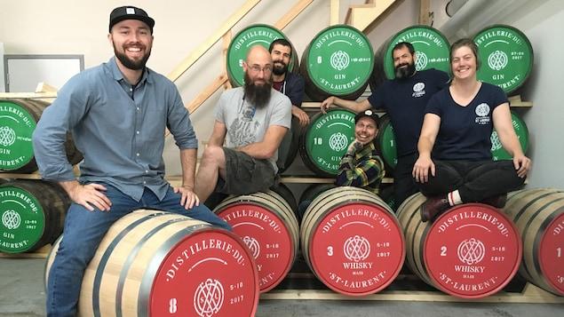 Joël Pelletier, copropriétaire de la Distillerie du St. Laurent, et toute son équipe sont fièrement assis sur leurs nouveaux barils de whisky.