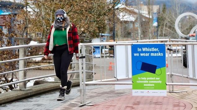 Une femme portant un masque marche près d'une clôture où une affiche encourage à porter le masque.