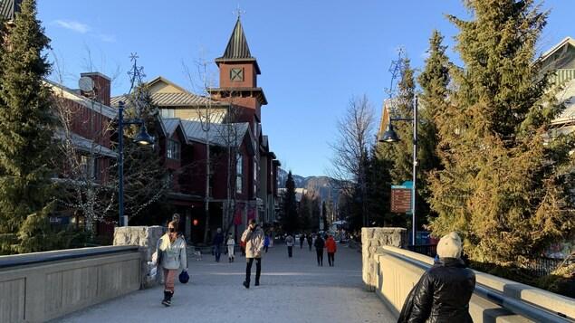 Des gens traversent un pont piétonnier dans le village de Whistler.