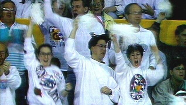 Des hommes et des femmes debout dans un aréna portent du blanc et brandissent des pompons blancs.