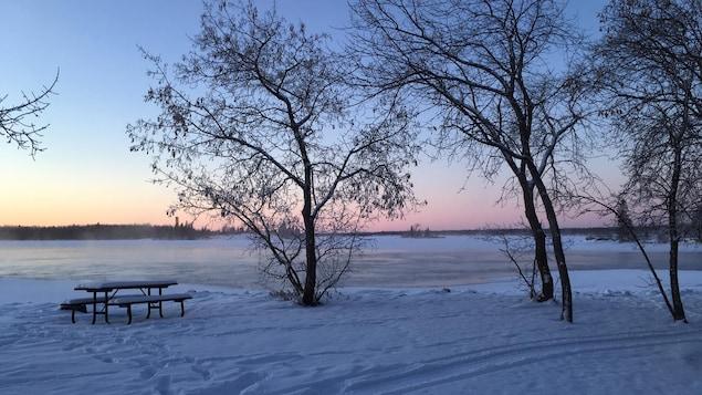 Vue sur un lac presque tout gelé en hiver, à partir d'un terrain de camping.