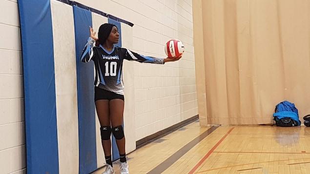 Whitney Ashu est photographiée dans un gymnase alors qu'elle s'apprête à faire un service au volleyball.