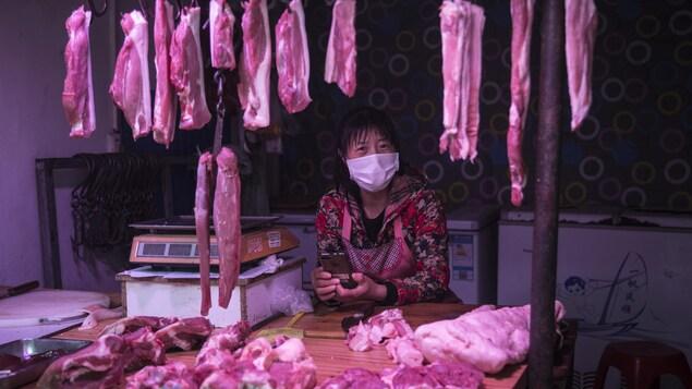 Une femme consulte son téléphone cellulaire au milieu de pièces de viande suspendues à des crochets.