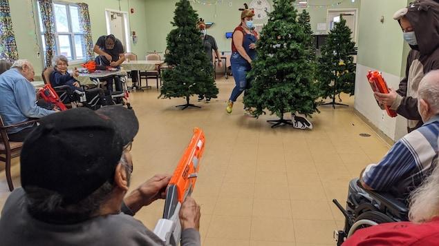 Des ainés visent avec un pistolet jouet une employée de la résidence déguisée en chevreuil.