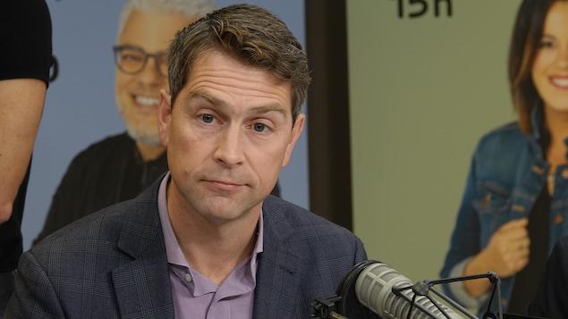 M. Amos participe à un débat dans le studio radio de Radio-Canada avec les autres candidats dans la circonscription.