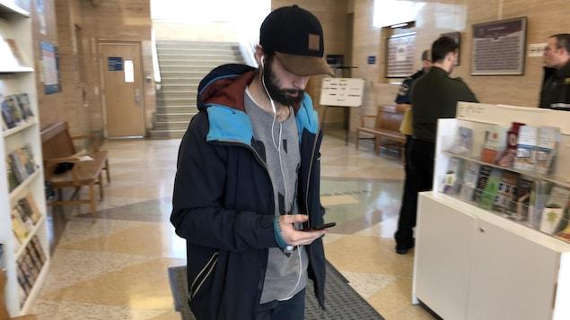 Un homme sort du palais de justice en regardant son téléphone, la tête baissée sous une casquette.