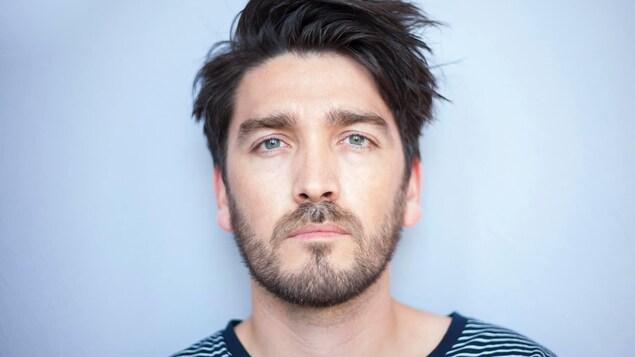 Un homme barbu pose devant un fond blanc et fixe la caméra.