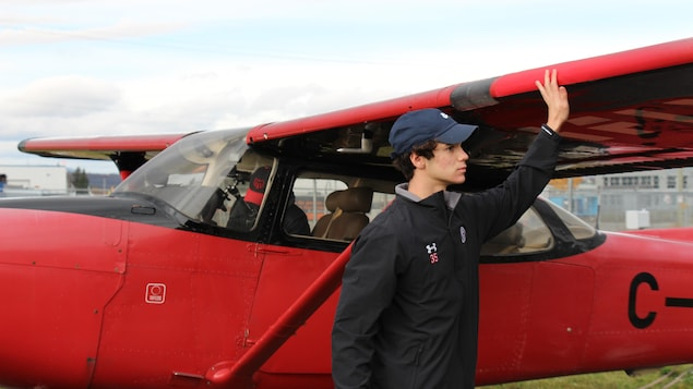 William Rousseau inspecte l'aile d'un petit avion rouge.