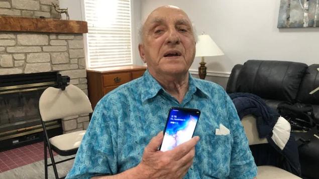 Un vieil homme avec une chemise bleue avec son téléphone cellulaire en main.