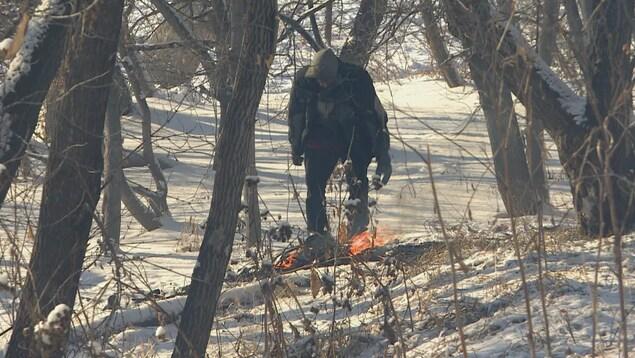 Un homme au milieu d'arbres et devant un feu dans la neige.