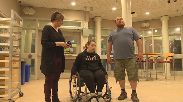 Jerzee Wasylnuk sur son fauteuil roulant entouré  de son père et de Jocelyne Gagnon à l'entrée de la cafétéria de l'Université de Saint-Boniface.