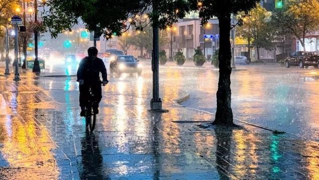 Un cycliste roule sous la pluie à Winnipeg.