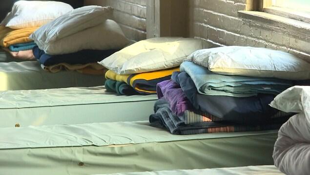 Des couvertures, des oreillers et des serviettes sur des lits dans un refuge.