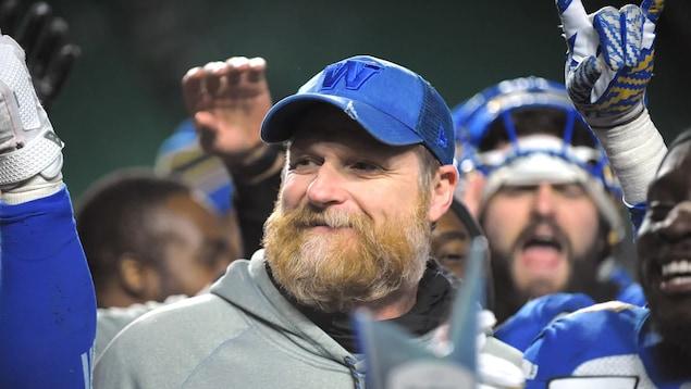 Mike O'Shea souriant entouré de ses joueurs.