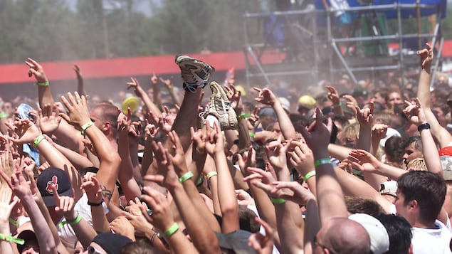 Une foule de personnes assistent à un concert extérieur.
