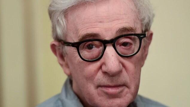 Portrait de Woody Allen, qui porte des lunettes aux montures noires et une chemise grise.