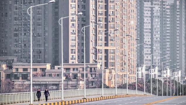 Des personnes portant un masque marchent dans les rues désertes de Wuhan.