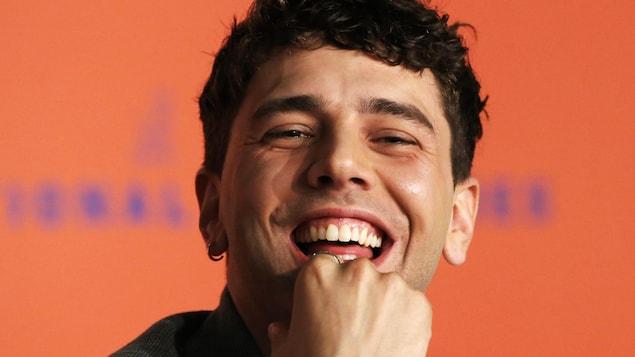 Xavier Dolan sourit à pleines dents.