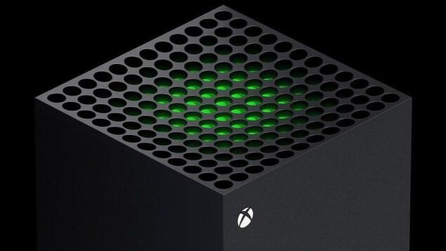 Le haut de la console Xbox Series X. Il s'agit d'une tour noir avec une grille, à travers laquelle passe une lumière vert lime.